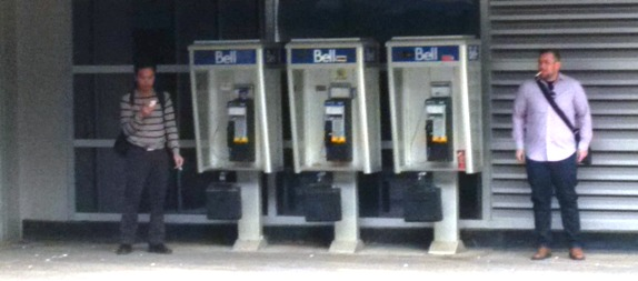 Fewer people are using payphones, although many still take shelter in their presence.
