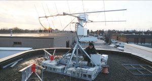 A technician works with satellite technology and other equipment on a rooftop. Cheaper Telecom Service from Cellphone Towers in Space