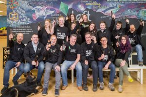 photo shows several staff members holding beer bottles, toasting the viewer