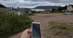 picture shows person's hand, holding a smartphone in remote region
