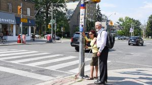 People waiting at urban intersection; man holds assistaive walking cane.