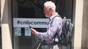 Man holds smartphone in front of CNIB Hub doorway.