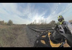 ATV drives alongside railroad tracks in summer scene