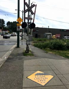 sidewalk decal alerts pedestrians to rail crossing ahead
