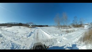 ATV driver approaches railway crossing in wintertime
