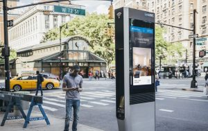 man checking his smartphone stands near electronic kiosk in New York City