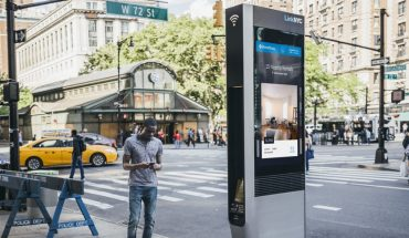 man checking smartphone stands near electronic kiosk in New York City