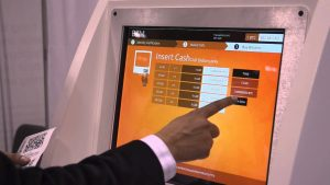 man's hand points at automated teller machine screen