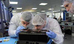 technicians in white suites and hairnets work on small electronic object