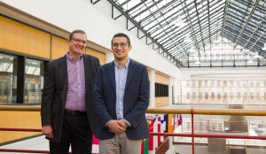 two male professors standing in university atrium
