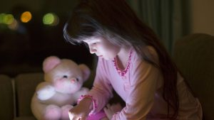 young child's face illuminated by smartphone screen
