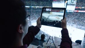 Fan looks at digital tablet screen during NHL hockey game.