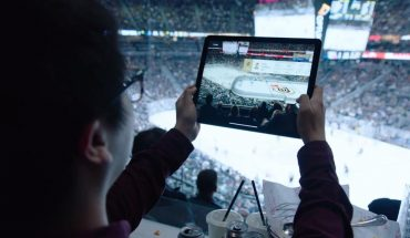 fan in stands at NHL hockey game holds up digital tablet with sports on screen