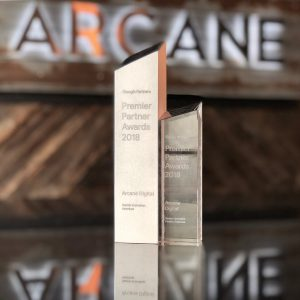 engraved glass award pictured in front of Arcane name