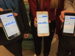 three people stand together, each holding a smartphone