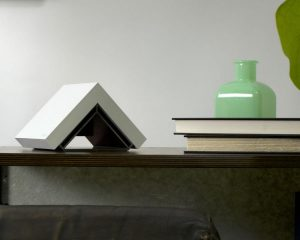 small triangular computer device sits on table top next to books, lamps