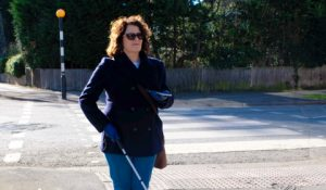 woman walks along city street with a white cane and smartphone in her hands