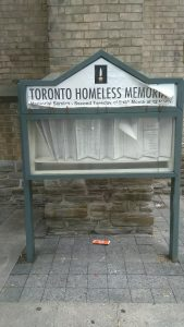 homeless memorial sign in front of brick wall