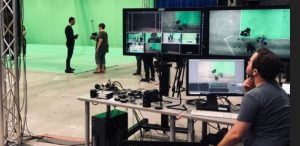 Inside a high-tech media studio, man sits in front of several TV screens and monitors, watching actors in background.