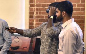 two men use virtual reality goggles in classroom