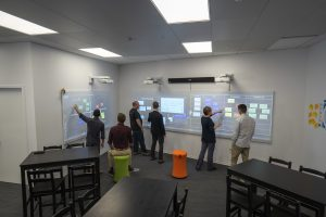 men and women at work in technically-sophisticated classroom environment