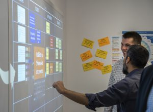 businessmen standing and working at interactive white board wall