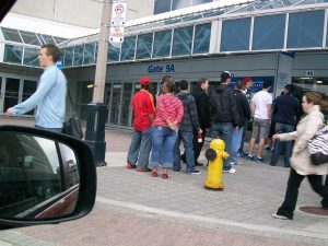 fans lined up outside large arena ticket wicket