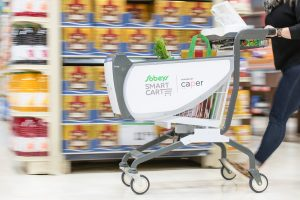 shopping cart pushed by grocery store aisles