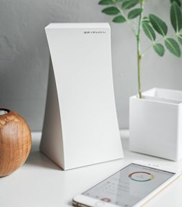 white Gryphon device sits on desktoip; smartphone and planter nearby