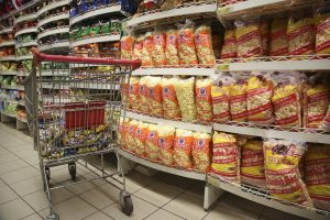 shopping cart near shelves of snack foods in grocery store