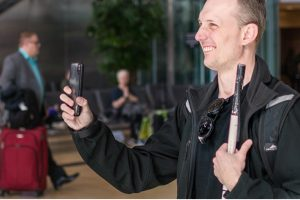 man with white cane using smartphone and assistive tech