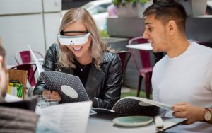 seated man and woman talking; woman wears electronic eyewear