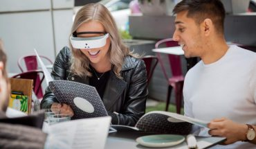 seated man and woman talking; woman wears electronic eyewear
