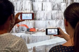 two people point smartphones at giant photo mural