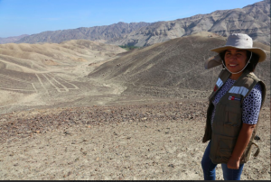 female naturalist stands on Nazca plain in Peru
