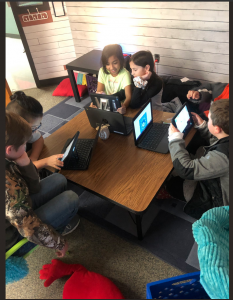 young students gather around table while using smartphones and app