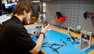 male technician works at repair shop bench