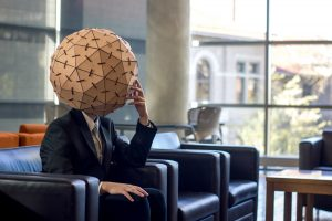 man in suit seated on sofa, wearing large bamboo helmet