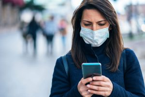 woman wearing medical mask looks at smartphone