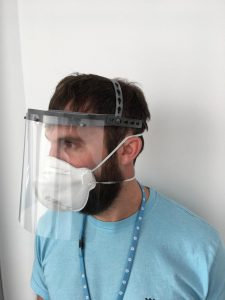 man wearing face shield, mask, hospital gown