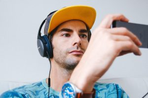 wearing headset, young man looks at smartphone