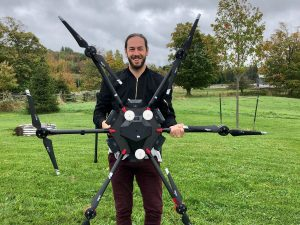 smiling man holds large drone while standing outdoors