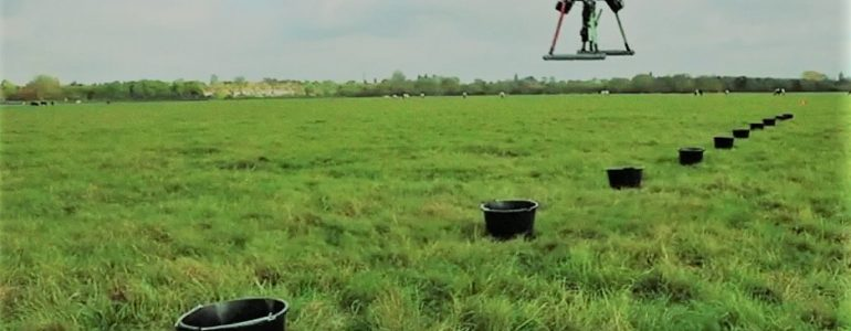 drones hover over open field above row of targets