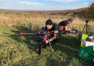 two men working on large drones in outdoor setting