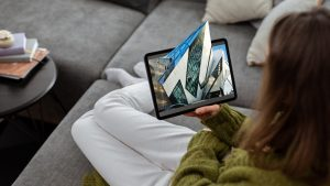 young woman looks at digital tablet while at home, ROM image on the screen