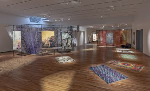 musem spaces has woven rugs, clothes and tapestries on display