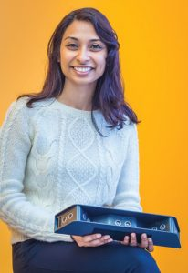 woman holds tech gadget