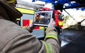 fireman holds laptop near fire truck