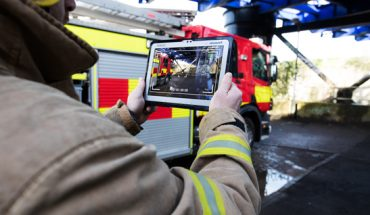 fireman holds laptop near fire truk