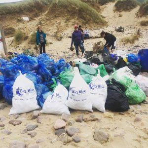 bags and bags of plastci wastr e gathered on beachfront